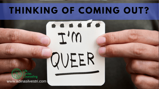 Human hands holding a note up with the phrase, 'I'm Queer.""